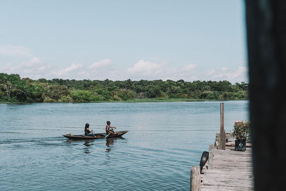 Crianças ribeirinhas usando um dos principais meios de transporte na Amazônia.
